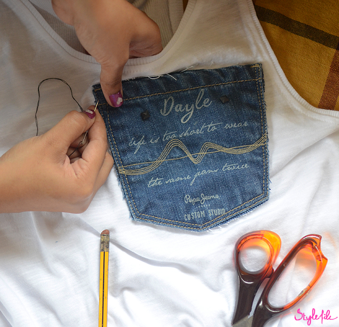 Women's fingers with nail art stitching the denim pocket on a white t-shirt surrounded by a scissor and pencil for the DIY tutorial of the Denim Pocket Patch