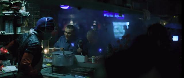 vemos luces de neón al fondo, dos policías con placas luminosas, en la barra  comiendo fideos, el cocinero con mascarilla, es de noche