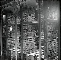 A black and white photo of an historic library showing towering bookcases of old books, with a man finding one.