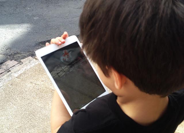 Imagem de criança jogando Pokémon Go no tablet, tentando capturar uma Goldeen.
