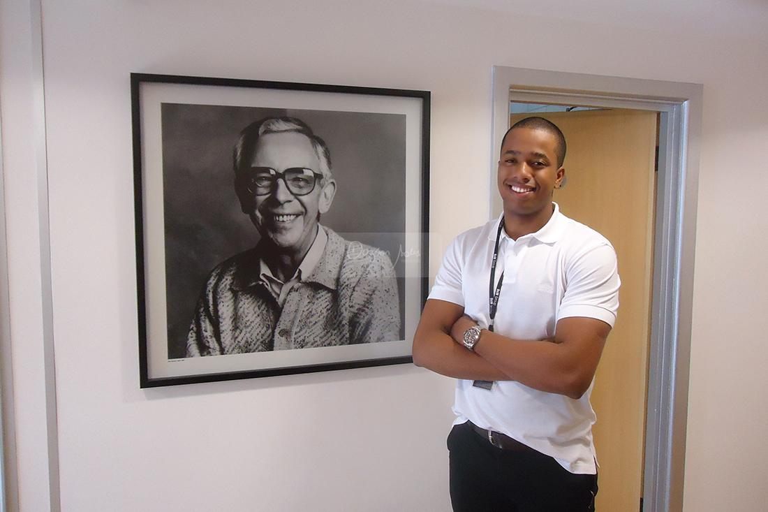 Dagson Sales posa ao lado de fotografi de John Bowers, fundador da B&W Bowers & Wilkins