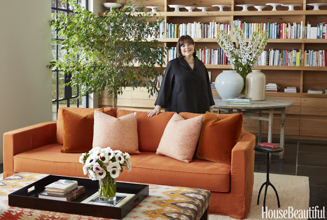 Ina Garten standing near bookshelves and orange sofa in East Hampton home