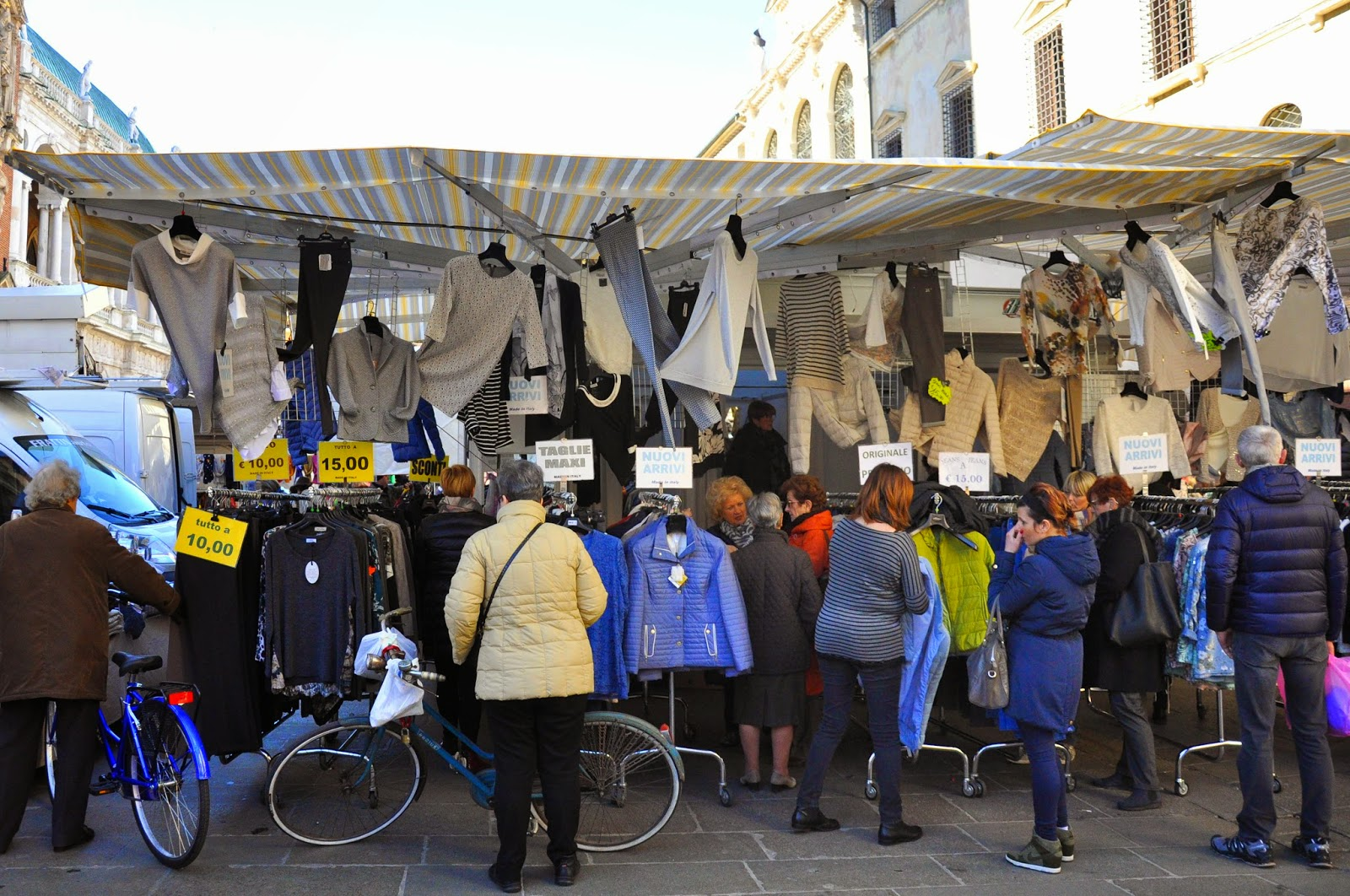 Clohes hanging underneath a stall's marquee at the Thursday market in Vicenza, Italy