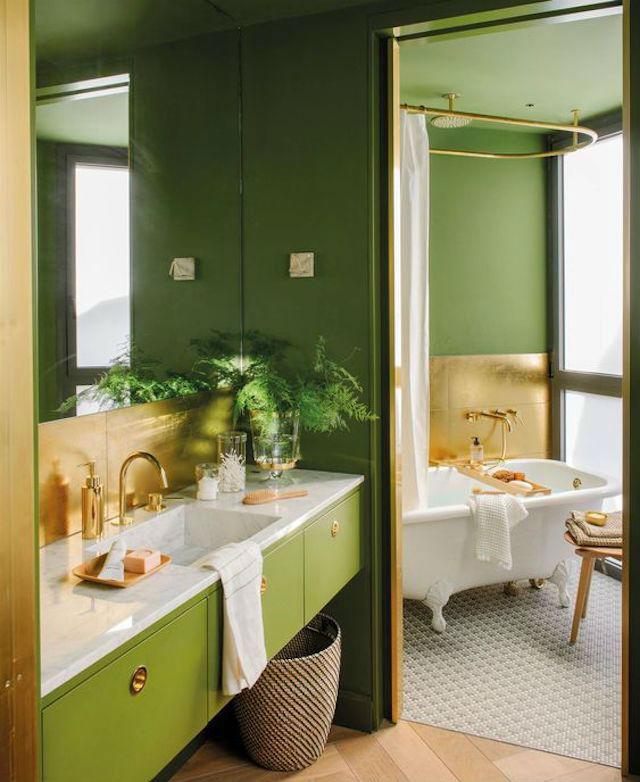 Baño pintado de verde oscuro (color 2018), con encimera de mármol y detalles en color dorado (tiradores, grifos, frontal, jabonera...)