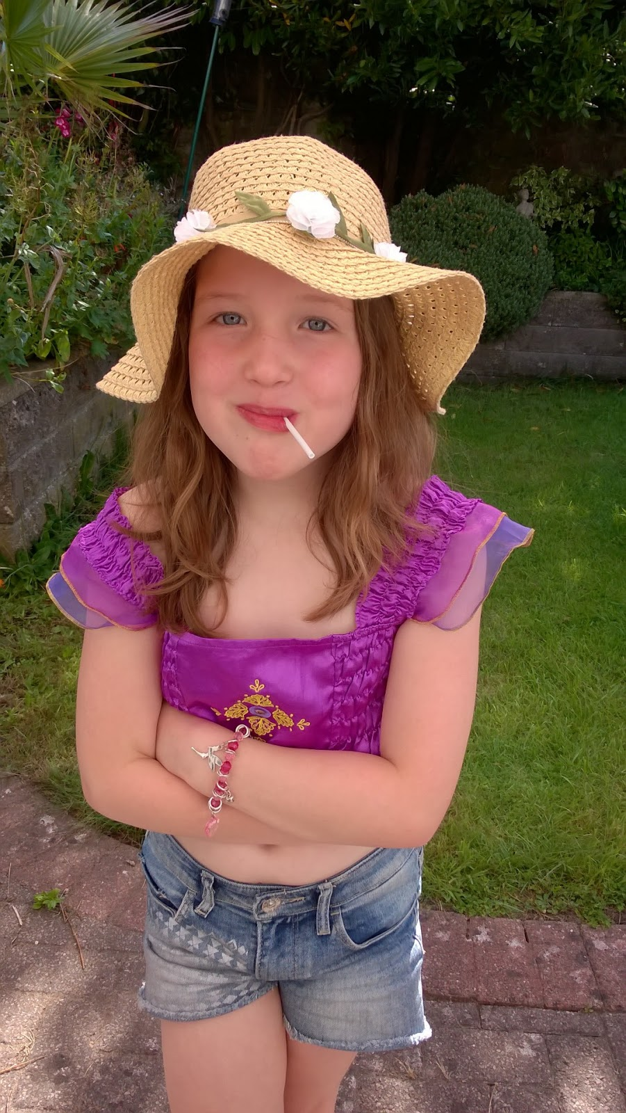 left out on a playdate - Caitlin in the garden wearing a floppy sunhat