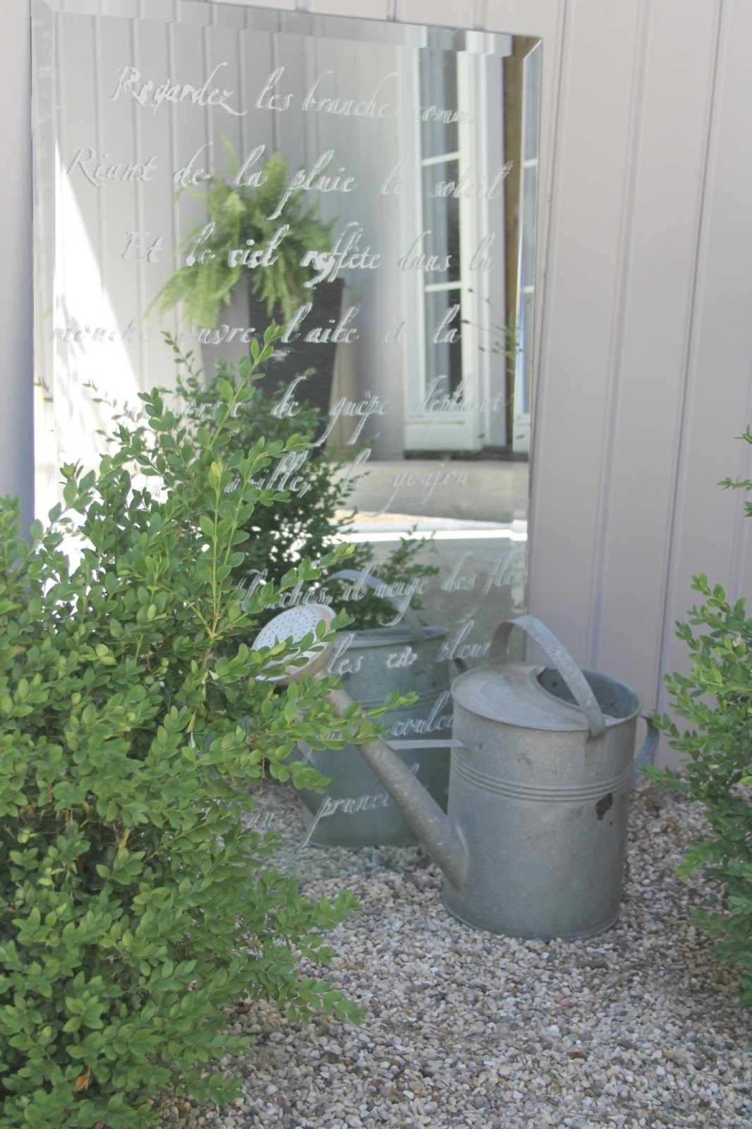 French farmhouse decor style in a courtyard garden with pea gravel, a vintage watering can, and a mirror stenciled with a French poem. #hellolovelystudio #frenchcountry #frenchfarmhouse #courtyard #stenciled #mirror