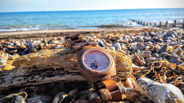 wooden watch on some driftwood with pebbles and a blue sea