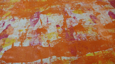 a colorful piece of paper with orange, yellow and magenta paint on it
