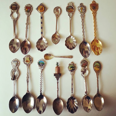 Fifteen vintage souvenir teaspoons arranged in rows on a white background