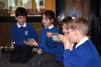 Pupils hand round a bag containing moth poo