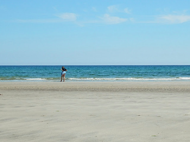 Girl on beach when tide out at Pentewan, Cornwall