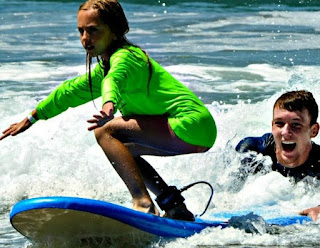 Aloha Beach Camp female camper learning to surf while her camp counselor guides the back of her surfboard.