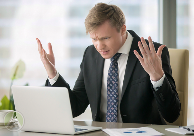 frustrated businessman reading email on laptop in office