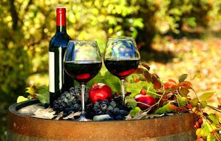 Μπουκάλι-κρασιού-και-δύο-ποτήρια-με-κόκκινο-κρασί-επάνω-σε-ξύλινο-βαρέλι.