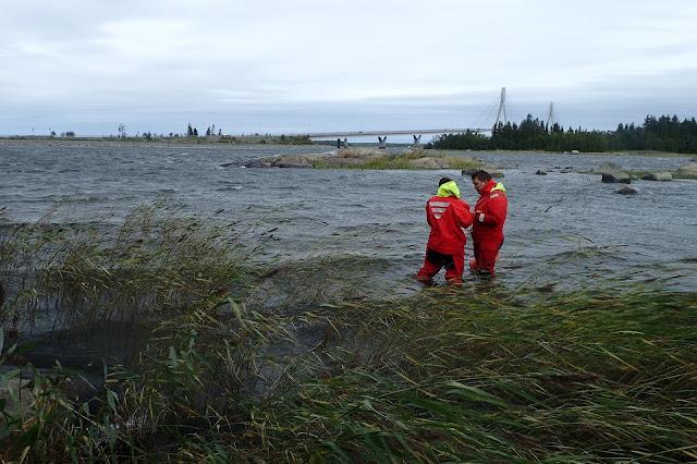 Kaksi pelastautumispukuista henkilöä tuulisessa meressä seisomassa