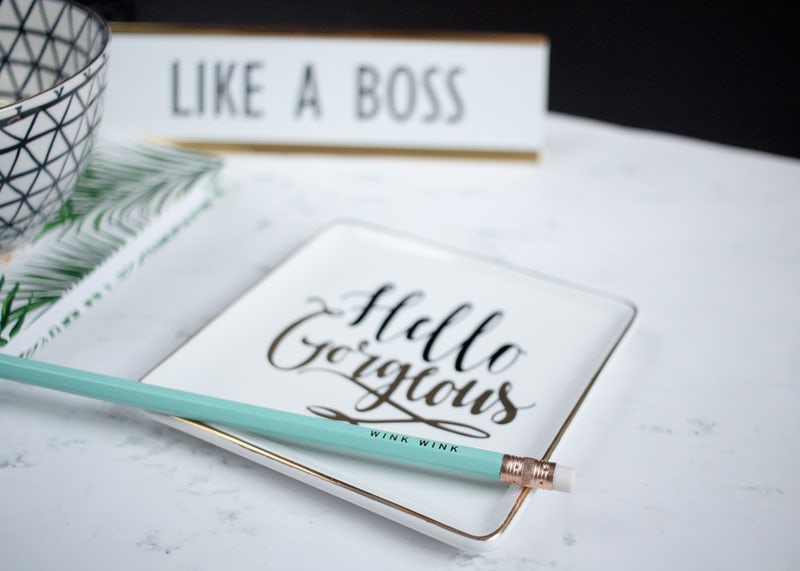 blogger's desk area with a girl boss plaque and tray for organisation