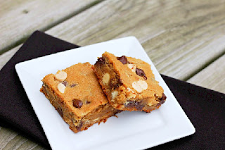 2 peanut butter chocolate chip blondies on a white plate with black napkin