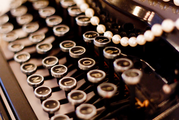 Pearls stung across the vintage typewriter are an elegant addition.