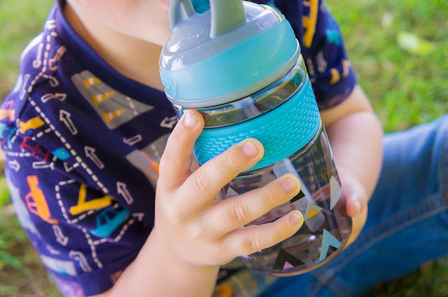 close up of childs hands holding nuby water bottle