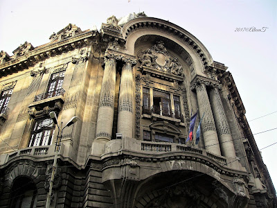 "In the old center. The Bourse Palace.  The style is the neo-classical French with pilasters and corinthian columns. ""Palatul Bursei"" is a building in Bucharest, built between 1906 and 1912, according to the plans of the architect Ştefan Burcuş. Stil artistic al cladirii: Eclectic de factură academică, neoclasic Data începerii construcției: 1906 Data finalizării: 1912"