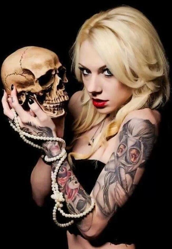 Espectacular mujer rubia sosteniendo una calavera, lleva tatuajes de craneos en el brazo