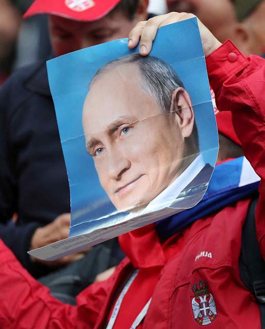 O cartaz não e segurado por um torcedor da Rússia, mas da Sérvia. O objetivo visado foi além do esporte
