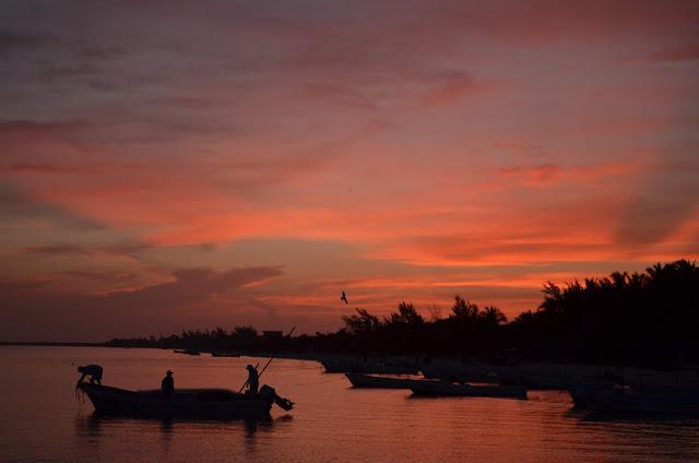 Atardecer en la isla de Holbox en Mexico, Colores anaranjados y pescadores