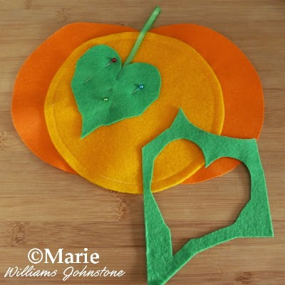 A felt pumpkin with green leaf pinned on