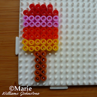 rainbow bead colors on white pegboard