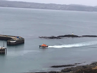 rnli mallaig lifeboat coming in to rural harbour