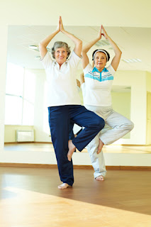 Photo of two senior women doing a tree pose in yoga
