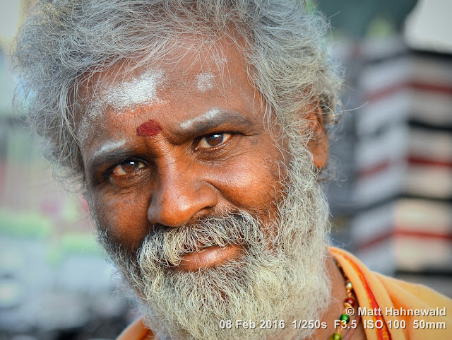 Matt Hahnewald Photography; Facing the World; closeup; street portrait; headshot; outdoor; Asia; South Asia; India; Tamil Nadu; Tiruchirappalli; Srirangam; Ammamandapam; ghats; Nikon D3100; Nikkor AF-S 50mm f/1.8G; travel; travel destination; beggar; photography; colour; portraiture; person; people; eyes; eye contact; Indian man; grey hair; face; grey beard; poor; horizontal; ethnic; modern India; vibhuti; red tilaka mark