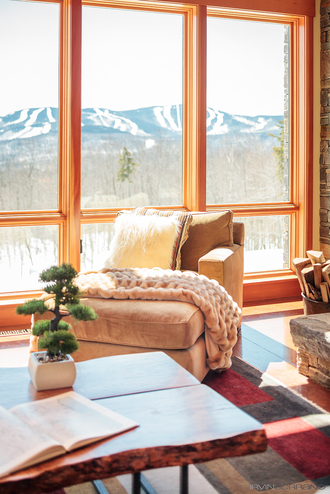 Faux fur accent chair sits near large windows overlooking the mountains in Newry, Maine.