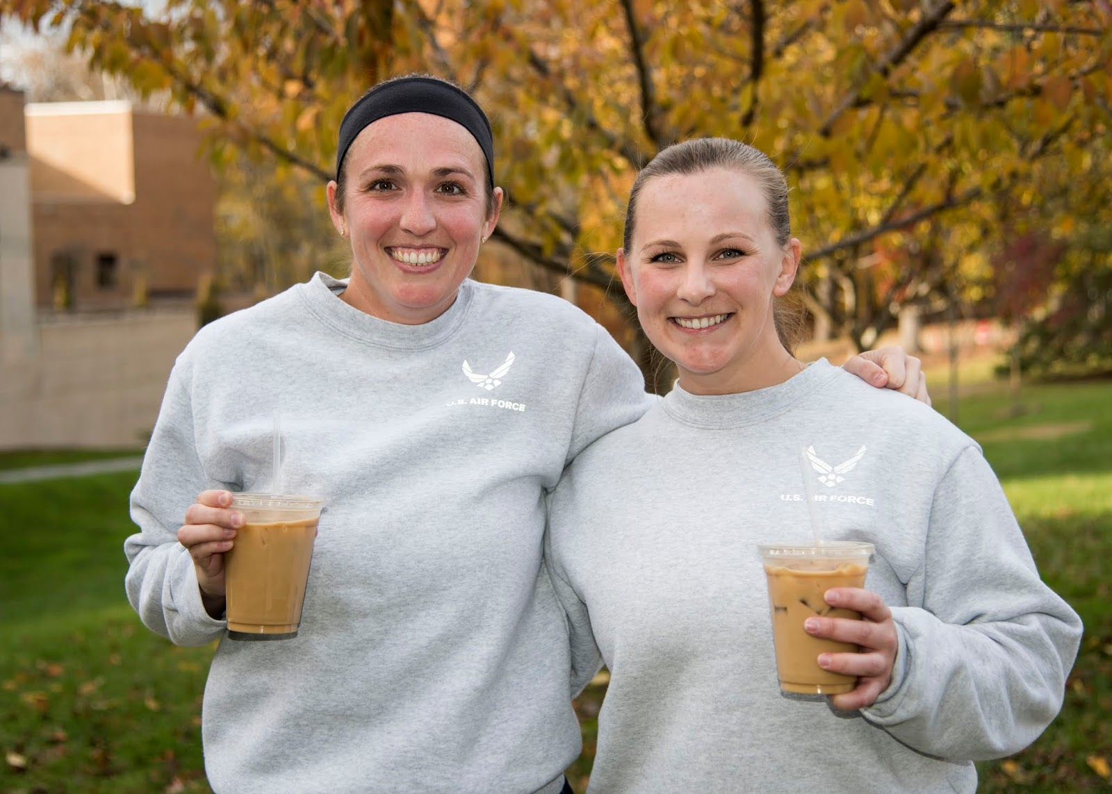 Two female Airmen are embracing each other with coffee in opposite hands. They are posing for a photo outside in front of the woods.