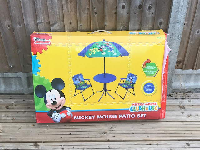 A yellow and red box with a picture of the patio set, Mickey Mouse and other Disney branding