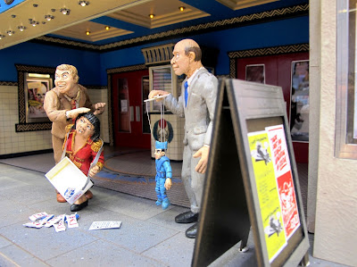 Three figures in front of a modern dolls' house miniature cinema lobby. One man is attacking an usherette, the other is holding a marionette.
