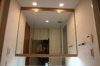 洗面台の左右の壁にエコカラットプラス 石目長のレリーフがあるあわいベージュのストーンⅡの303角を平張りにしました。