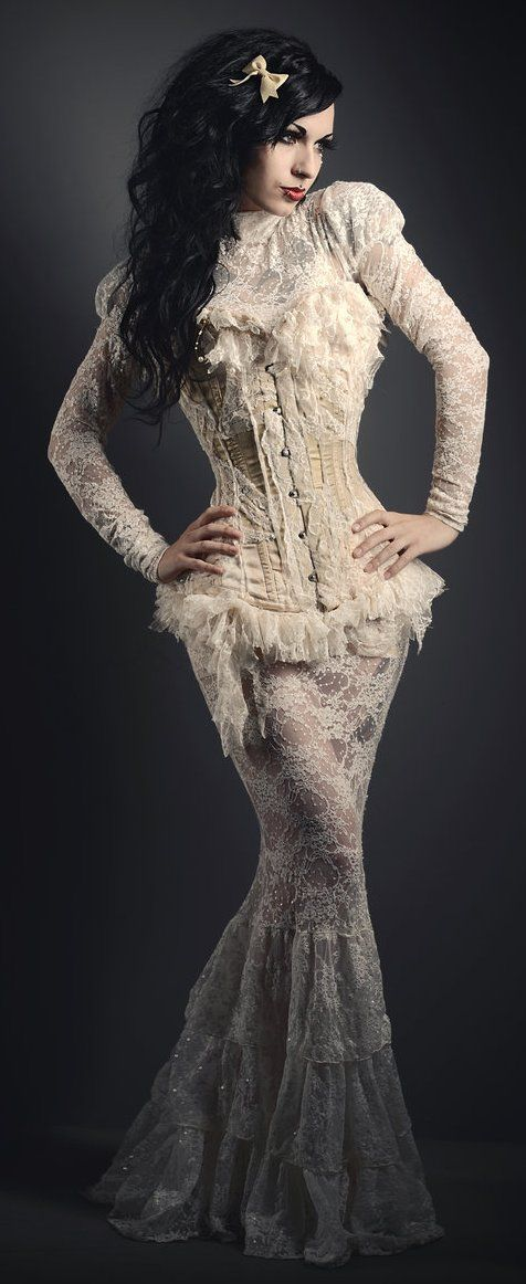 Woman wearing a neo-victorian wedding dress with a steamgoth/steampunk/gothic/goth influence. White lace wedding dress with leg of mutton sleeves and high victorian collar/high neck. Floor length mermaid/fishtail skirt with ruffles. Sexy ivory lace overbust corset.