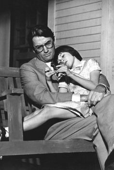 film image of Gregory Peck and Mary Badham on a front porch swing