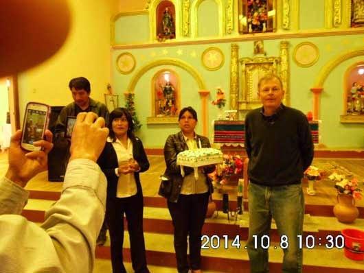 Eine Torte wird von dem Lehrerkollegium des Gymnasiums in der Kirche überreicht