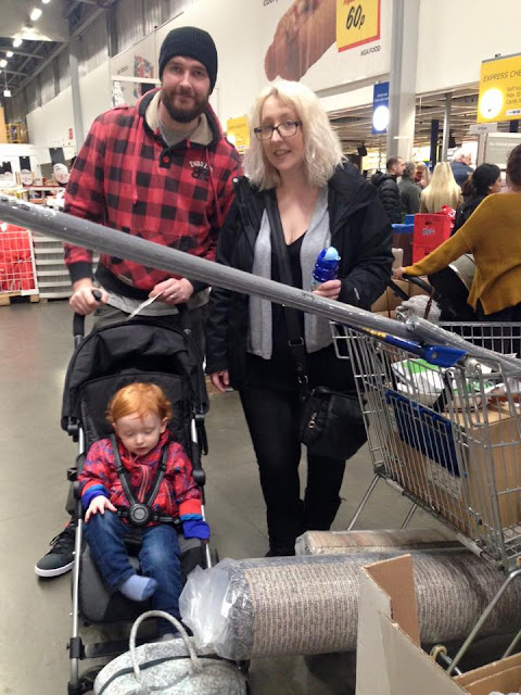 A man, woman and a child in a pushchair with a trolley full of ikea products