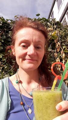 Hier drink ik een beker groene shake in de tuin.