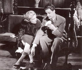 Madeleine Carroll removes her stockings while handcuffed to Robert Donat