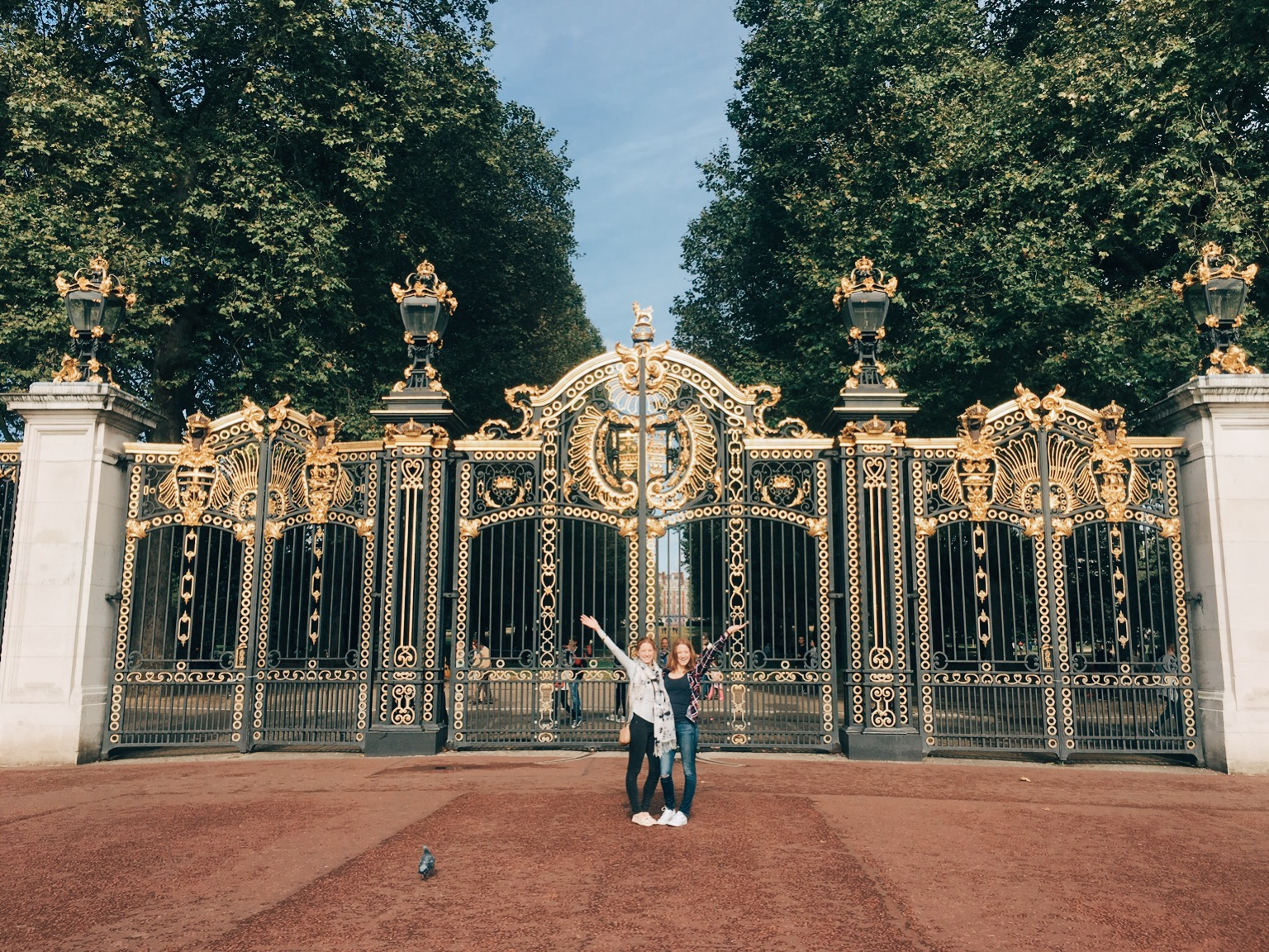Tourists pose in front of Buckingham Palace in London