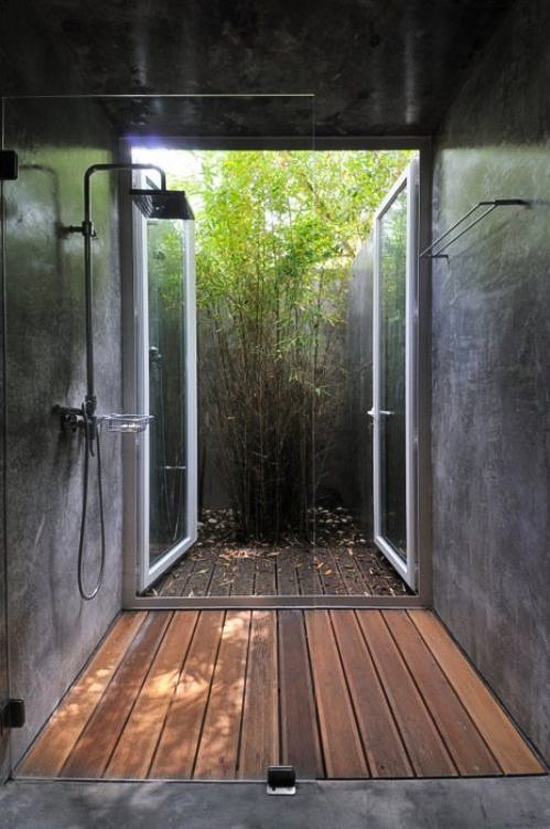Wooden deck shower with concrete walls and a view to the small yet vibrant patio designed by FVA Architects via Designboom.