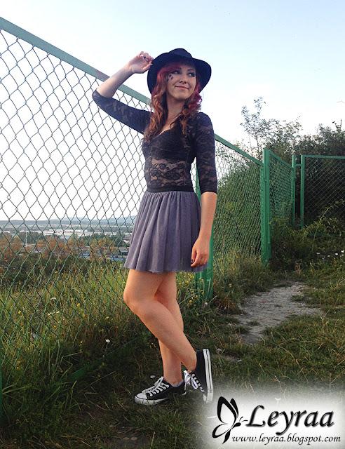Czarne koronkowe body, tiulowa szara spódnica, klasyczne czarno-białe trampki, czarny kapelusz, gwiazdki robione eyelinerem