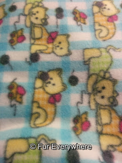 A fleece blanket with a kitten pattern on it.