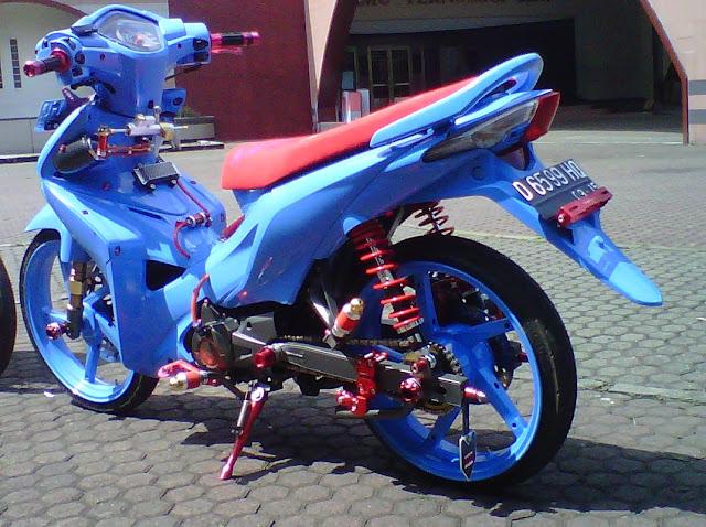 Foto Modifikasi Honda Revo Full warna di bagian seluruh bodi motor dibalut dengan airbrush warna biru muda termasuk juga pada lingkar pelek pun juga diubah warna biru untuk bagian jok tipis berwarna merah yang terlihat garang serta shocbreaker hingga aksen dibagian bawah mesin motor