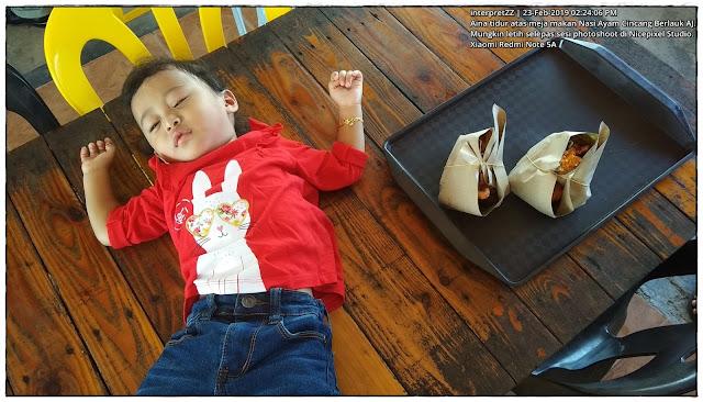 gambar kanak-kanak perempuan memakai baju kanak-kanak merah, seluar denim kanak-kanak biru tidur atas meja makan di Nasi Berlauk Ayam Cincang AJ.