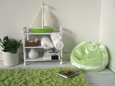 Corner of a one-twelfth scale modern miniature holiday house with a green fluffy rug, bean bag and a shelf holding towels and books.